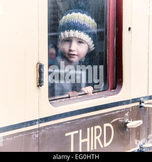 Boy (6-7) looking out train window - Stock Photo