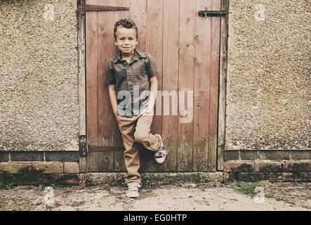 Portrait of boy in front of old stable at farm - Stock Photo