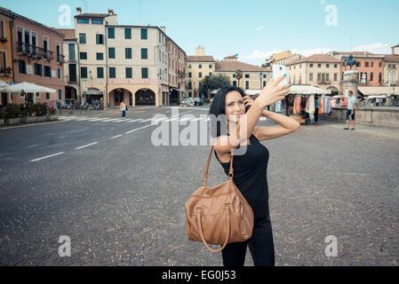 Italy, Padua, Young woman taking selfie - Stock Photo
