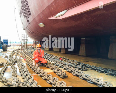Dock worker in a shipyard talking on a walkie talkie - Stock Photo