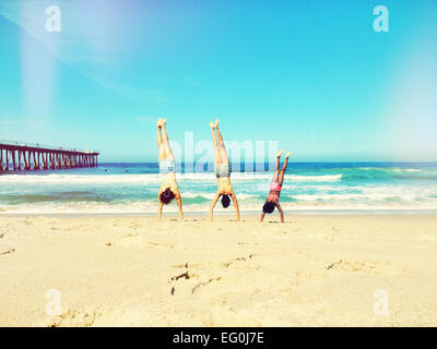 Mother, father and daughter doing handstand on beach - Stock Photo