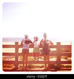 Three girls standing by a fence looking at the ocean, california, America, USA - Stock Photo