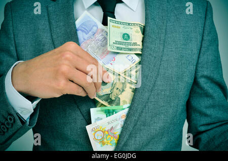 man in suit putting euro, dollar and pound bills in his jacket, depicting concepts such as greediness, corruption - Stock Photo