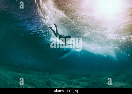 Surfer duck diving under a wave, Hawaii, America, United States - Stock Photo