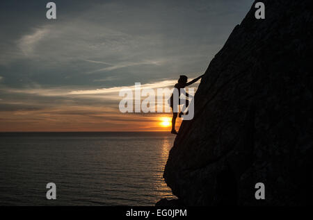 Silhouette of woman climbing cliff at sunset, Galicia, Spain - Stock Photo