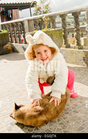 Girl playing with ginger cat on terrace - Stock Photo