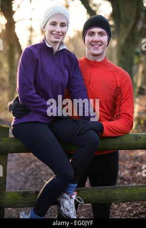 Portrait Of Couple On Winter Run Through Woodland Sitting On Fence - Stock Photo