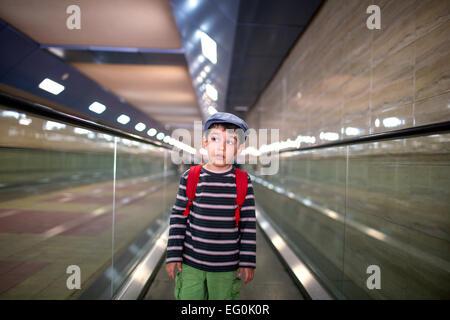 Bulgaria, Sofia, Boy (4-5) standing on escalator - Stock Photo