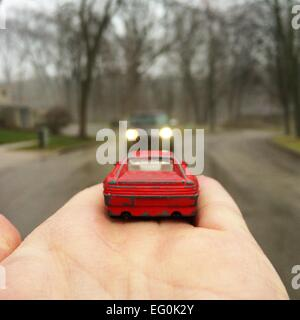 Toy car in man's hand facing a real car in the street - Stock Photo
