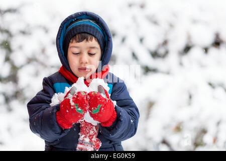 Bulgaria, Sofia, Young boy (4-5) holding snow - Stock Photo