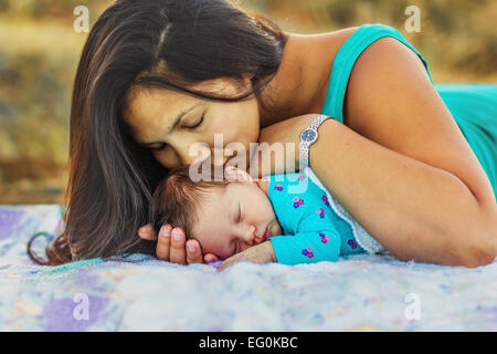 Mother kissing her newborn daughter - Stock Photo
