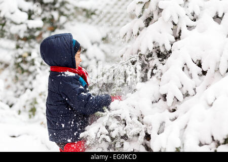 Young boy (4-5) playing outside in winter - Stock Photo