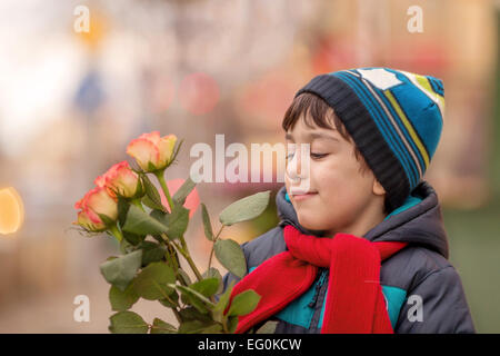 Young boy (4-5) holding roses - Stock Photo