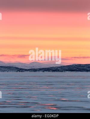 Sweden, Lapland, Sunrise over frozen lake of Tornetrask in Lapland Arctic - Stock Photo