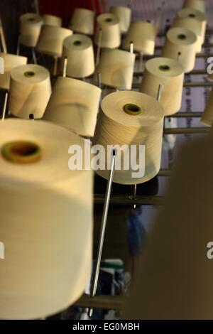 Dhaka 09 February 2015. Group of bobbin thread cones on a warping machine in a textile mill. - Stock Photo