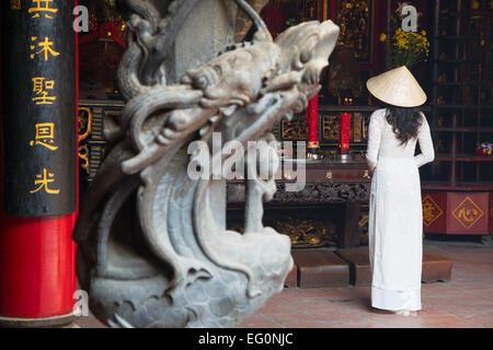 Woman wearing ao dai dress at Ha Chuong Hoi Quan Pagoda, Cholon, Ho Chi Minh City, Vietnam - Stock Photo