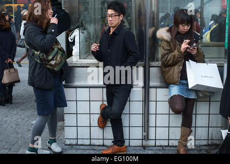 Youths smoking at a designated smaoking area at the Sibuya Crossing in Tokyo. Special smoking areas have been designated, - Stock Photo