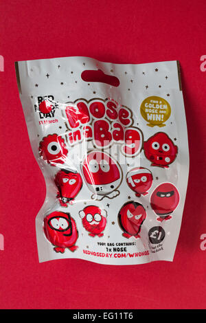 Nose in a Bag find a golden nose and win ready for Red Nose Day on 13 March for Comic Relief isolated on red background - Stock Photo