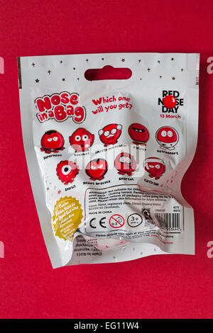 Nose in a Bag which one will you get ready for Red Nose Day on 13 March isolated on red background - Stock Photo