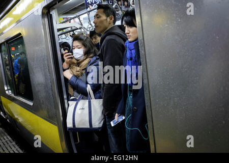 Commuters crowded onto the Tokyo subway. The combined subway network of the Tokyo and Toei metros comprises 290 - Stock Photo