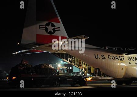 U.S. Air Force Airmen unload a U.S. Coast Guard C-130 Hercules aircraft Jan. 16, 2010 at Port-Au-Prince airport - Stock Photo