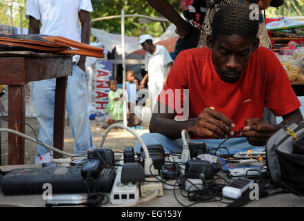 A displaced Haitians man fixes mobile phones in a tent city near, the Presidential Palace in Port au Prince, Haiti - Stock Photo