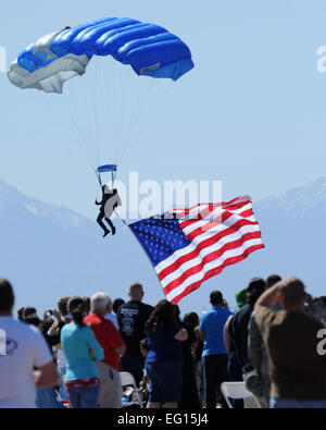 Air show spectators look on as a cadet with the U.S. Air Force Academy Wings of Blue parachute demonstration team - Stock Photo
