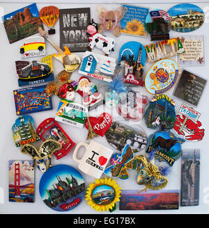 Assortment of travel and quirky fridge magnets on a fridge door - Stock Photo