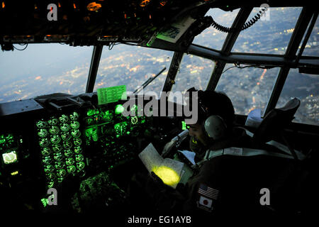 YOKOTA AIR BASE, Japan -- Capt. Yuri Batten, 36th Airlift Squadron, looks at a map March 19 while flying on a C - Stock Photo