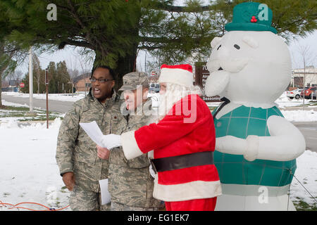 """U.S. Air Force Chaplain Maj. Obadiah Smith left, Col. William T. Cahoon and Santa Claus sing """"Oh Christmas Tree"""" - Stock Photo"""