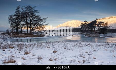 First light of the day casts a golden glow on the Hills above Rannoch Moor taken from the banks of a Frozen Loch Tulla Stock Photo