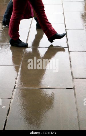 People walking on a wet pavement - Stock Photo