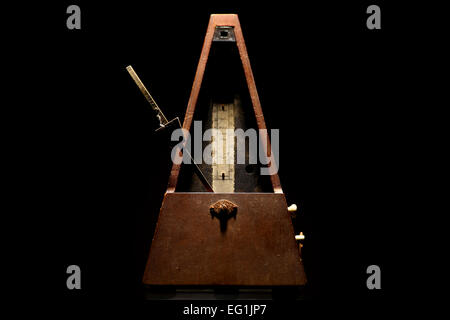 Vertical shot of a vintage metronome, on a black background. - Stock Photo