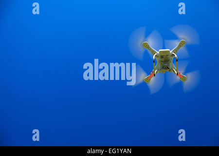 A view from below of a flying drone with a gimbal and camera attached. Drone, photography, flying, surveillance - Stock Photo