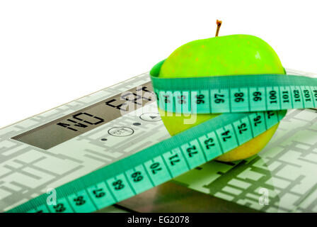 Apple and measure tape on weighing machine with sign no fat - Stock Photo
