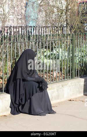 Muslim woman in a Burka sitting on the curb in London england - Stock Photo