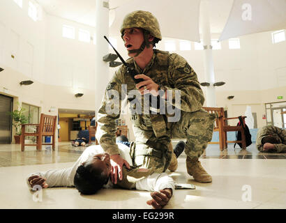 U.S. Air Force Staff Sgt. William Vernon calls for medical assistance during an active shooter exercise Feb. 14, - Stock Photo