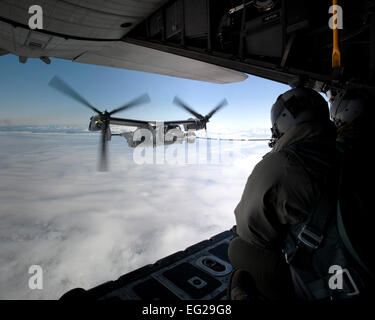 A CV-22B Osprey receives fuel from a MC-130H Combat Talon II June 21, 2013, off the coast of Greenland. The aircraft - Stock Photo