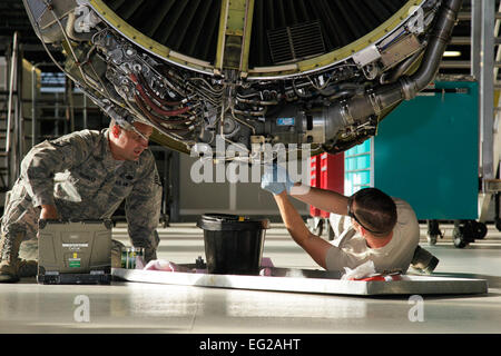 Staff Sgt. Brian Fielhauer and Senior Airman Otto Kelly service the engine of a KC-135 Stratotanker as part of the - Stock Photo