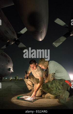 Staff Sgt. Kyle Law and Staff Sgt. Joshua Jorgensen, 774th Expeditionary Airlift Squadron crew chiefs, consult a - Stock Photo