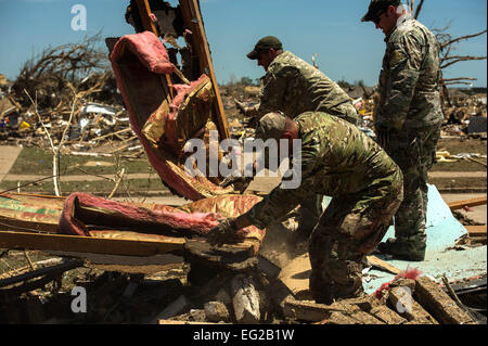 U.S. Air Force Capt. Van Blaylock, front, Tech. Sgt. Ben Lake, middle, and Tech. Sgt. Brandon White, back, help - Stock Photo