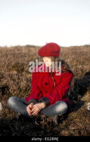 a girl in a red coat is sitting on a hill - Stock Photo