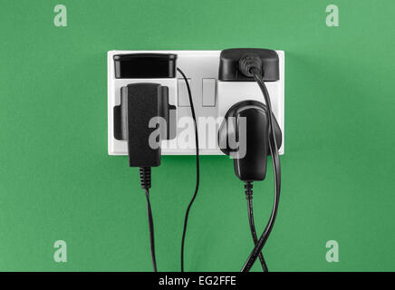 Battery chargers plugged in to outlet - Stock Photo