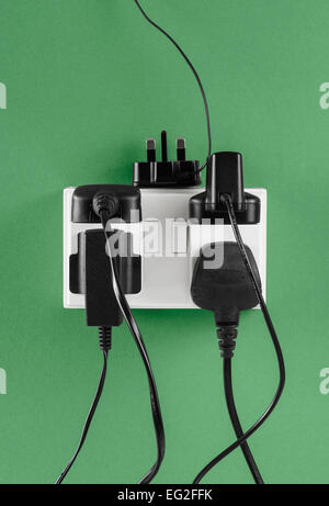 Multiple Chargers plugged in to Wall Socket - Stock Photo