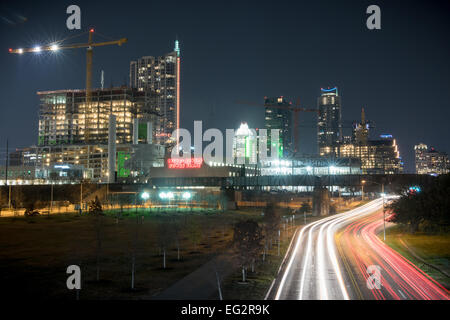 A night view of the skyline of Austin, Texas, USA with light streaks visible on Cesar Chavez Blvd. - Stock Photo