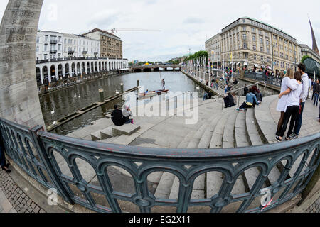 Young people relax and have fun on the embankment  Kleine Alster river , Hamburg, Germany , Europe - Stock Photo