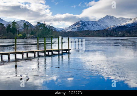 Derwentwater, Keswick, winter, two birds on partly frozen lake by wooden jetty, snow covered fells behind, Lake - Stock Photo