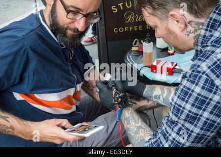 Tattoo artist Alex McWatt of Three Kings Tattoo applying a tattoo to the arm of a man who is checking his cellphone - Stock Photo