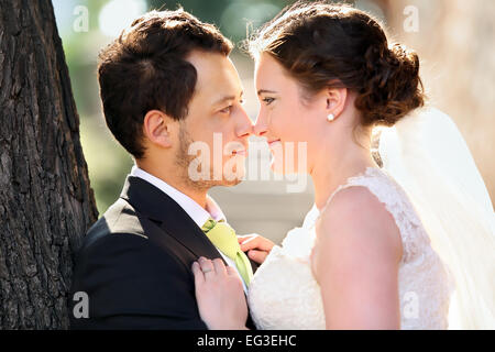Young couple after wedding in a hug face to face - Stock Photo