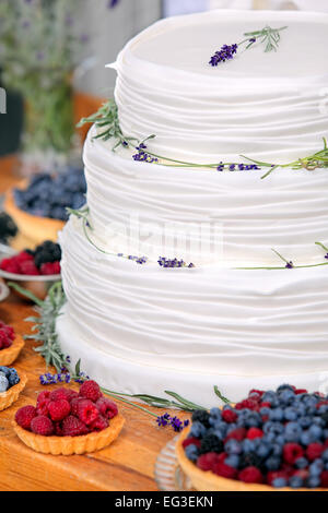 Wedding cake on wooden background with blueberries raspberries and lavender decoration - Stock Photo